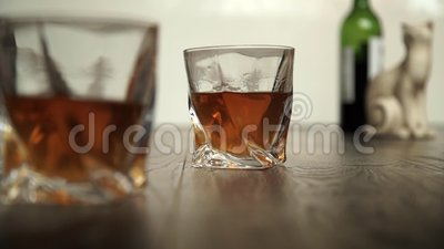 Pouring whiskey in two glasses stock video