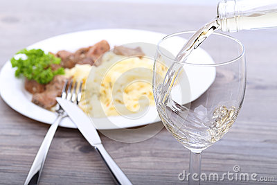 Pouring white wine and food background