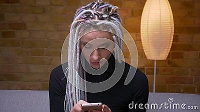 Pousse de plan rapproché du jeune hippie caucasien attirant femelle avec la transmission de messages blonde de dreadlocks au télé banque de vidéos