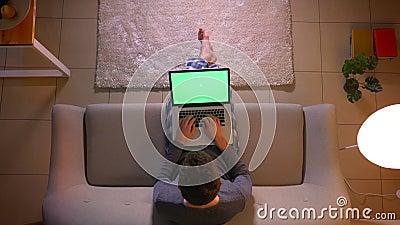 Pousse sup?rieure de plan rapproch? de transmission de messages de jeune homme sur l'ordinateur portable avec l'?cran vert tout e banque de vidéos