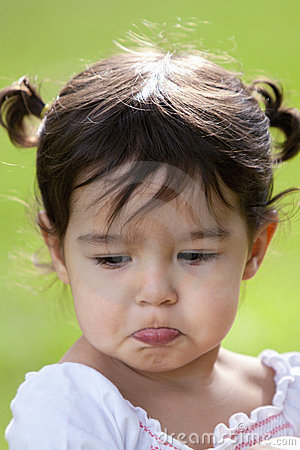 Pouting little girl outdoors