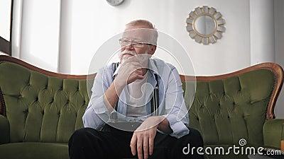 Povertà in salute, un vecchio affetto da emicrania per il mal di testa, per via della vita seduto sul divano nella stanza, concet stock footage