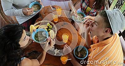 Povos que comem o alimento asiático delicioso da sopa de macarronetes, alimentação do grupo dos amigos opinião de Sit At Table To filme