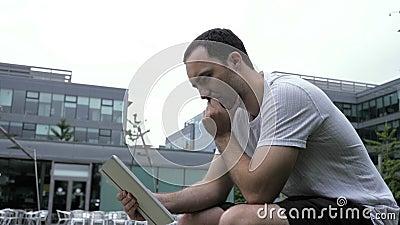 Poważny, przypadkowy mężczyzna używający cyfrowego tabletu siedzącego na zewnątrz zdjęcie wideo