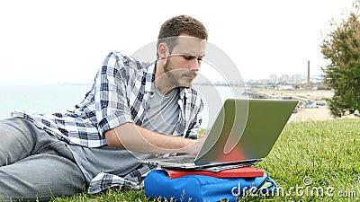 Poważny uczestnik kursu korzystający z notebooka na trawie zdjęcie wideo