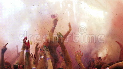 Powder is thrown at holi colour festival in slow motion. A colourful shot of music fans throwing coloured powder into the air at holi colour festival in slow