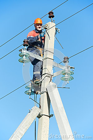 Power electrician lineman at work on pole