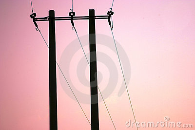 Power lines against sunset sky
