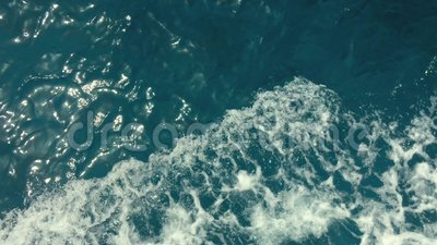 Powerful waves pulled out from fast moving boat, a huge stream of deep blue water with white foam rising up, steady. Beautiful shot, perfect for film, digital stock footage