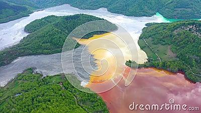 Powietrzny 4k trutnia widok kolorowego czerwień groszaka górniczy ścieki w kontraście z świeżym zielonym lasem zbiory wideo