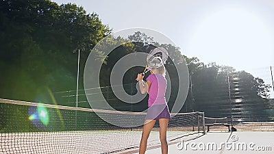 Prática atrativa da menina na batida usando uma raquete durante o treinamento vídeos de arquivo