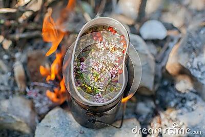 Préparation du thé sur le feu de camp.
