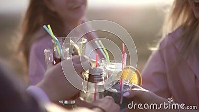 Próxima, mãos de meninas colidem óculos com coquetéis na rua cocktail urbano de Verão filme