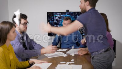 Pracownicy biura spotykają się i dyskutują w sali konferencyjnej, dwóch mężczyzn kłóci się i rzuca gazety zdjęcie wideo