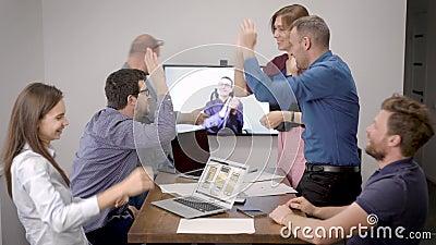Pracownicy biurowi komunikują się z szefem przez wideorozmowę, radość, świętowanie zwycięstwa w sali konferencyjnej zdjęcie wideo
