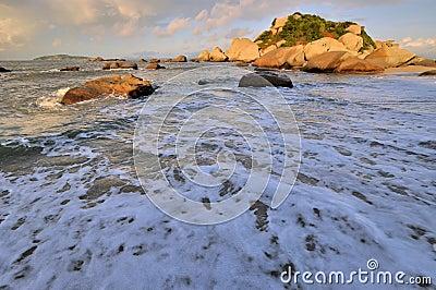 Praia larga do mar com a rocha no nascer do sol