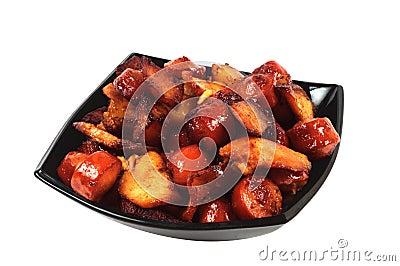 Prato com salsichas, carne e as batatas grelhadas.