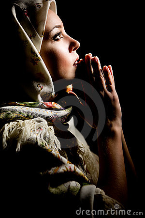 Praying girl with shawl on head. Retouched