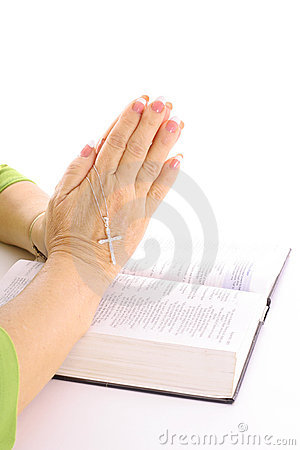 Praying hands over bible with rhinestone cross