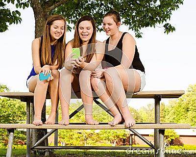 Pre-tienermeisjes die terwijl het hangen uit vooraan texting