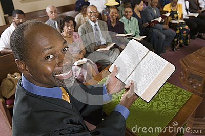 Preacher at altar holding open Bible in Front of Congregation portrait high angle view