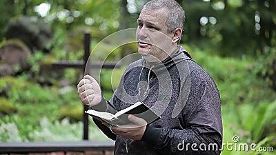 Prediker met Bijbel en rozentuin stock footage
