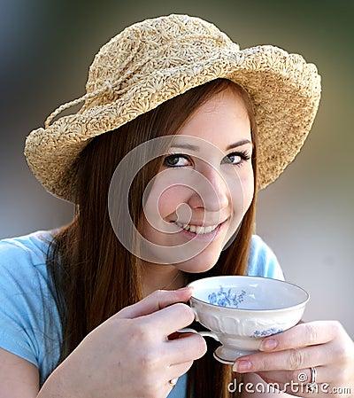 Preetty girl sips tea from English tea cup