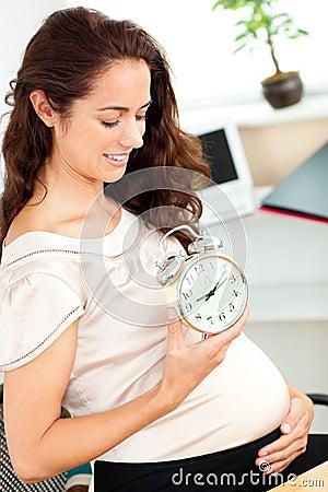 Pregnant businesswoman holding an alarm clock