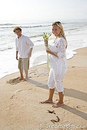 Pregnant couple on beach holding white flower