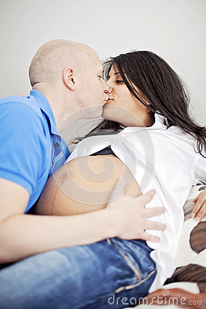 Pregnant couple kissing in bed