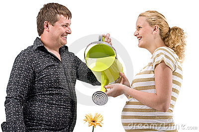 Pregnant couple waters flower