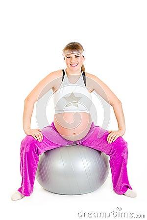 Pregnant female doing exercises on fitness ball