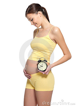 Pregnant female holding clock near the stomach