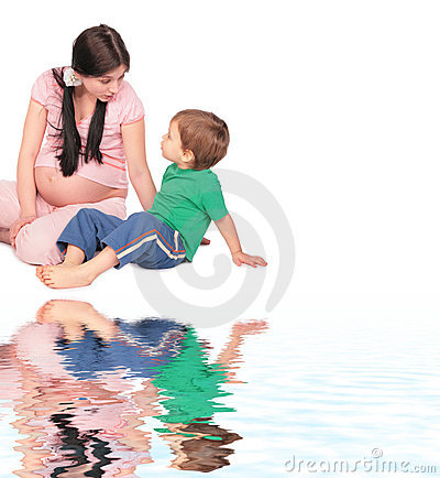 Pregnant girl with child sits on floor