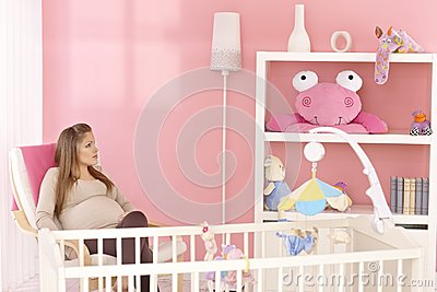 Pregnant mother sitting in baby s room