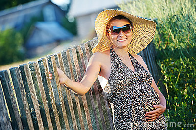 Pregnant smiling woman in field
