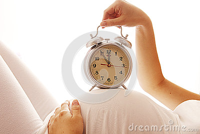 Pregnant Woman With An Alarm Clock On A White Background ...