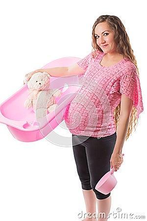 Pregnant woman bathe with toy Teddy bear in tub