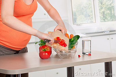 Pregnant woman cooking at kitchen