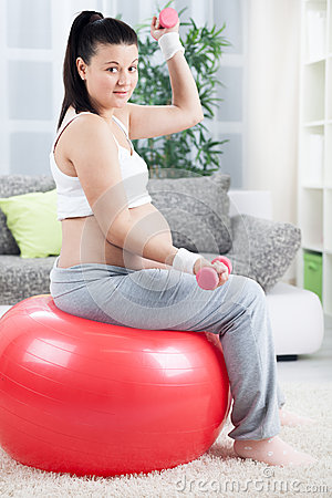 Pregnant woman doing bicep muscle exercises using dumbbells whil