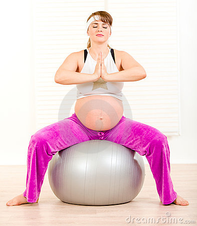 Pregnant woman doing pilates exercises on ball