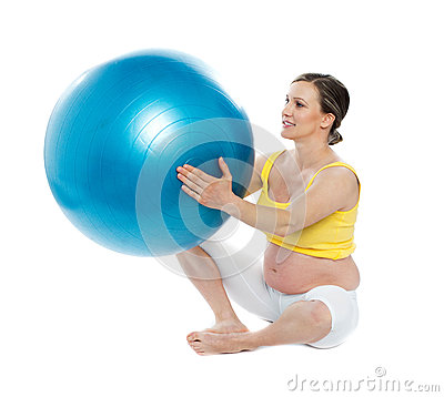 Pregnant woman excercises with a gymnastic ball