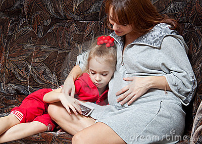 A pregnant woman with her daughter on the sofa