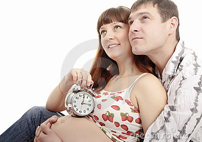 Pregnant woman and her husband holding alarm clock
