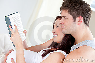 Pregnant woman and her husband reading a book