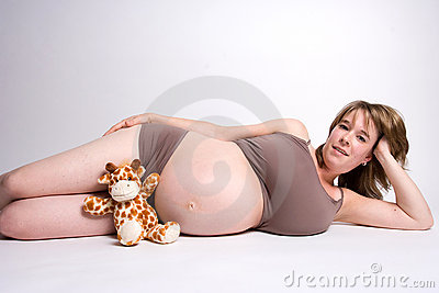 Pregnant woman on her side with a toy