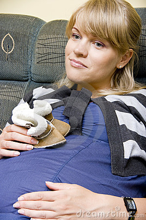 Pregnant woman hold baby shoes