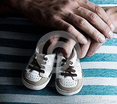 Pregnant Woman Holding Baby Shoes on her Belly