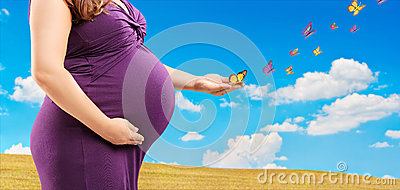 Pregnant woman holding her belly and butterflies on her hand, ou