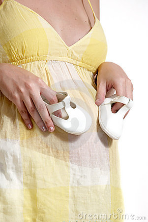 Pregnant woman holding pair of white shoes
